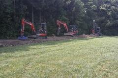 Kabelbau - Mit einem größeren Bagger wird der Rohrgraben erstellt. Nach dem Einbauen der Rohrleitung wird mit Kompaktbaggern  der Graben wieder verfüllt und verdichtet.