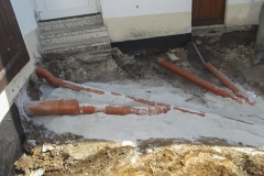 Kanalsanierung - Neu angeschlossene Abwasserleitungen im Sandbett verlegt. Die Rohre wurden zusammengeführt in einen separaten Schacht und mit einem elektrischen Rückstauverschluss (Rückstauklappe) versehen.