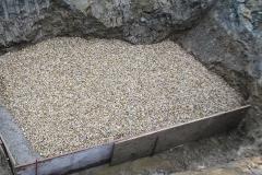 Quellfassung - Die wasserführende Schicht wird mit einer betonierten Umrandung eingefasst, in der sich auch die Quellleitung zur Wasserabführung befindet. Eine Kiesschicht wird zur Filterung eingebracht.