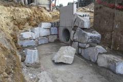 Einlaufbauwerk für Wasserkraftwerk - Nach Erstellen der Baugrube ist eine Betonsohle eingebaut worden, auf der die seitlichen Stützwände mit Wasserbausteinen errichtet wird. Diese hat den Zweck, die Wasserführung dauerhaft zu gewährleisten.