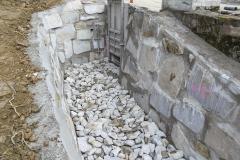 Einlaufbauwerk für Wasserkraftwerk - Hier zeigt das Bild die fertiggestellten Wände und eine Steinschüttung im Solbereich und im hinteren Bereich ein sog. Absperrschütz, um den Wasserfluss für Montagearbeiten im Kraftwerk zu unterbrechen.